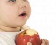 Little girl eating red apple